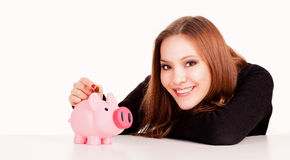 Woman putting coin in piggy bank Royalty Free Stock Image
