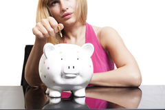 Woman putting coin in piggy bank Stock Photo