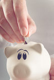 Woman putting coin in piggy coin bank Stock Images