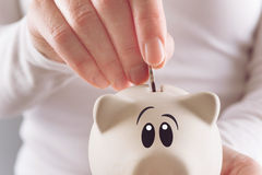 Woman putting coin in piggy coin bank Royalty Free Stock Photography