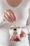 Woman putting coin in piggy coin bank Royalty Free Stock Photos
