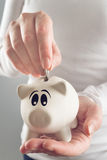 Woman putting coin in piggy coin bank Stock Image