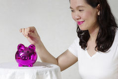 Woman putting a coin into money box Stock Photo