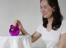 Woman putting a coin into money box. Woman putting a coin into piggy money box royalty free stock images