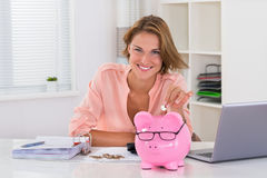 Woman Putting Coin In Piggybank Royalty Free Stock Image