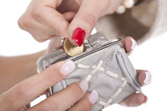 Woman putting a coin on the purse Royalty Free Stock Image
