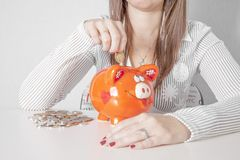 Woman putting coin into small piggy bank. Woman putting coin into small orange piggy bank.Money saving.n Royalty Free Stock Image