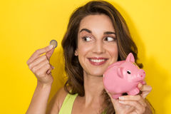Woman putting a coin in small piggy bank Royalty Free Stock Photography