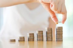 Woman Putting Coin To Rising Stack Of Coins. Close-up Of woman Putting Coin To Rising Stack Of Coins stock images