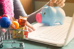 Woman putting coins in piggy bank, saving money for Christmas an stock photography