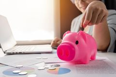 Woman putting coins into Pink Piggy Bank. royalty free stock photo