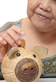 Woman putting coins in small piggy bank. Royalty Free Stock Photography