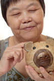 Woman putting coins in small piggy bank. Royalty Free Stock Images