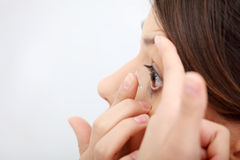 Woman putting a contact lens Stock Image