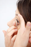Woman putting a contact lens Royalty Free Stock Photo