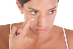 Woman putting on contact lens. Es Stock Photo