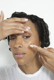 Woman Putting On Contact Lens. African American woman inserting a contact lens over white background Royalty Free Stock Photos