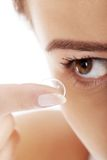 Woman putting contact lens in her eye Royalty Free Stock Photos