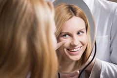 Woman putting in contact lens. At optician's office Stock Photography