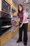 A woman putting cookies in oven stock images