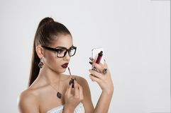 Woman putting, correcting red lipstick lip gloss stock images