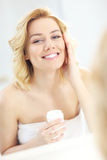 Woman putting on cream in bathroom Royalty Free Stock Photography