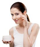 Woman putting on cream from container on face Royalty Free Stock Photography