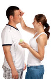 Woman putting cream on her boyfriend's face royalty free stock photo