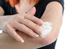 Woman putting cream on her elbow. Woman putting relaxing cream on her elbow Royalty Free Stock Photography