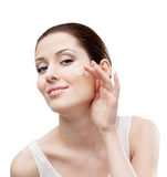 Woman putting on cream on her face Stock Image