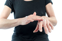 Woman putting cream on her hand Royalty Free Stock Image