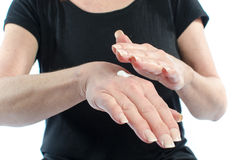 Woman putting cream on her hand Stock Photography
