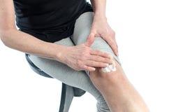 Woman putting cream on her knee Stock Photo