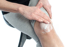 Woman putting cream on her knee Royalty Free Stock Images
