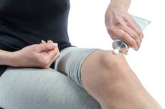 Woman putting cream on her knee Stock Photography