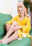 Woman putting cream on legs Royalty Free Stock Photos