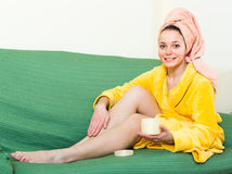 Woman putting cream on legs Royalty Free Stock Photography