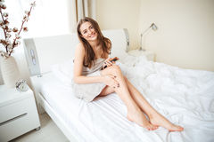 Woman putting cream on legs Royalty Free Stock Images