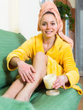 Woman putting cream on legs Stock Images