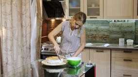 Woman putting cream on a sponge cake by hand using pallete knife. Cake on a rotating stand to decorate cakes. Cooking cake stock video footage