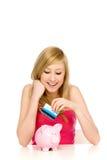 Woman putting credit card into piggy bank Royalty Free Stock Photos