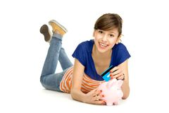 Woman putting credit card into piggy bank Royalty Free Stock Images