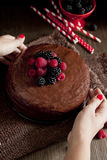 Woman putting a dark chocolate cake on table Royalty Free Stock Image