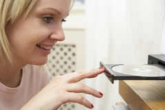 Woman Putting Disc In DVD Stock Image