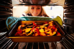 Woman Putting Dish Of Vegetables Into Oven To Roast Stock Photos