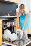 Woman putting dishes in the dishwasher Royalty Free Stock Photos