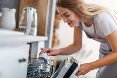 Woman putting dishes into dishwasher stock image