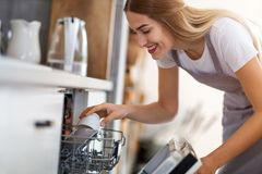 Woman putting dishes into dishwasher stock images
