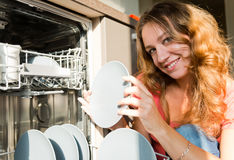 Woman putting dishes in the dishwasher Royalty Free Stock Images