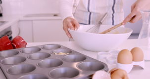 Woman putting dough in muffin mold stock video footage